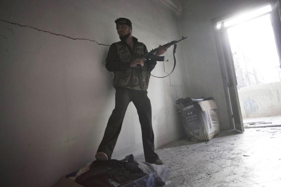 Free Syrian Army soldier takes cover while fighting against Syrian Army troops in Aleppo, Syria, Tuesday, Oct. 2, 2012. (AP Photo/ Manu Brabo)