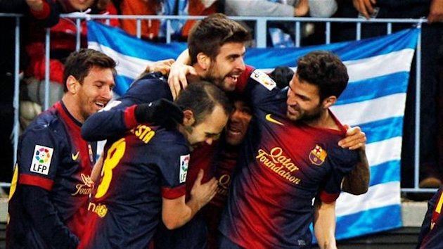 Barcelona's Gerard Pique is congratulated by team-mates after scoring a goal against Malaga (Reuters)