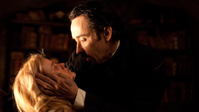 "In this film publicity image released by Relativity Media, John Cusack portrays Edgar Allan Poe, right, and Alice Eve portrays Emily Hamilton in a scene from the gothic thriller ""The Raven."" (AP Photo/Relativity Media, Larry Horricks)"