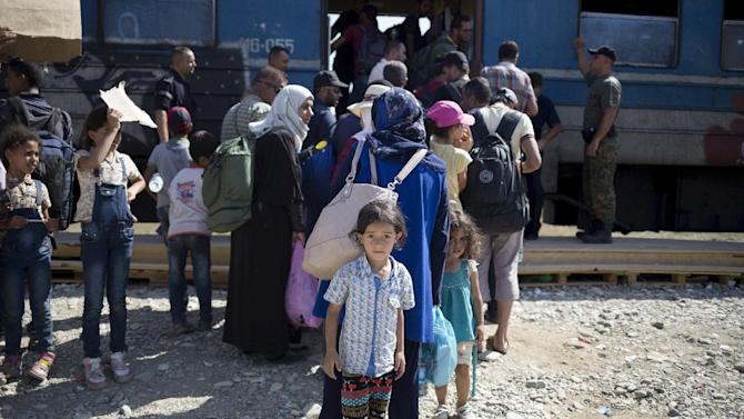 Migrant girl looks on as she waits to board a train after crossing the Macedonian-Greek border near Gevgelija