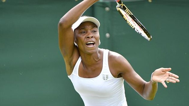 Venus Williams of the U.S. hits a return to Elena Vesnina of Russia during their women's singles tennis match at the Wimbledon tennis championships in London June 25, 2012