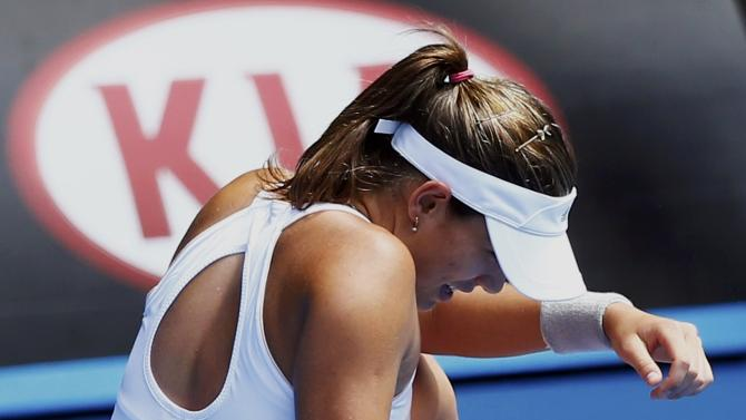 Muguruza of Spain falls after trying to hit a return to Williams of the U.S. during their women's singles fourth round match at the Australian Open 2015 tennis tournament in Melbourne