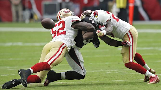 Arizona Cardinals running back Andre Ellington (38) is unable to hold onto the ball as San Francisco 49ers inside linebacker Patrick Willis (52) and Jimmie Ward (25) defend during the first half of an NFL football game, Sunday, Sept. 21, 2014, in Glendale, Ariz
