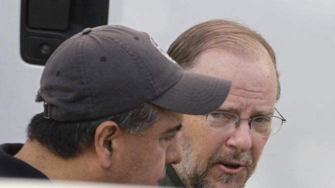 Former Enron CEO Jeffrey Skilling, right, partially shown behind a wall, arrives at the Bob Casey Federal Courthouse for a resentencing hearing Friday, June 21, 2013, in Houston. His original sentence of 24 years is expected to be reduced to between 14 and 17.5 years. His resentencing is part of a court-ordered reduction of his prison term and a separate agreement with prosecutors that will allow for the distribution of around $41 million in restitution to victims of Enron's collapse. (AP Photo /Houston Chronicle, Melissa Phillip )