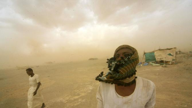 File picture of gold mine workers walking to their shelter during a sandstorm in Al-Ibedia locality at River Nile State