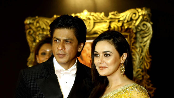 """In this Monday, Nov. 12, 2012 photo, Bollywood star Shah Rukh Khan, left, poses with fellow actor Preity Zinta during the premiere of his film """"Jab Tak Hai Jaan"""" or """"As long as I Am Alive"""" in Mumbai, India. Bollywood stars turned out in strength at the premiere of the movie for a final homage to movie mogul Yash Chopra, who died last month days after finishing the film. Chopra was known as the """"King of Romance"""" for creating classic love stories that were immensely popular. (AP Photo/Rafiq Maqbool)"""