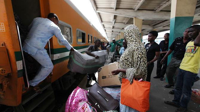 In this Photo taken, Friday, March . 8, 2013, passengers board an Ooni of Ife train to Kano, in Lagos, Nigeria.  Nigeria reopened its train line to the north Dec. 21, marking the end of a $166 million project to rebuild portions of the abandoned line washed out years earlier. The state-owned China Civil Engineering Construction Corp. rebuilt the southern portion of the line, while a Nigerian company handled the rest.( AP Photo/Sunday Alamba)