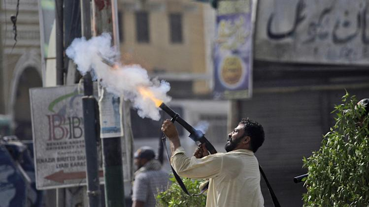 "In this Wednesday, May 2, 2012, photo, a plainclothes Pakistani police officer fires a tear gas canister at a hideout of criminals, during a crackdown operation against criminals in Karachi, Pakistan. For months, the Supreme Court's Chief Justice Iftikhar Chaudhry has been leading special hearings on Karachi's crime, berating the city's top police officers for failing to act. The past week, he demanded they move in to clean up so-called ""no-go"" areas _ entire neighborhoods where police fear to tread _ according to local press reports. (AP Photo/Shakil Adil)"