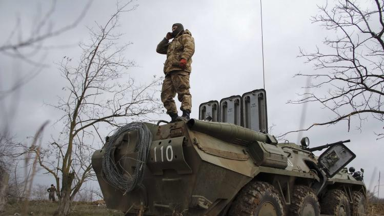 Ukrainian soldier stands on a military vehicle at a checkpoint at the road near a Crimea region border