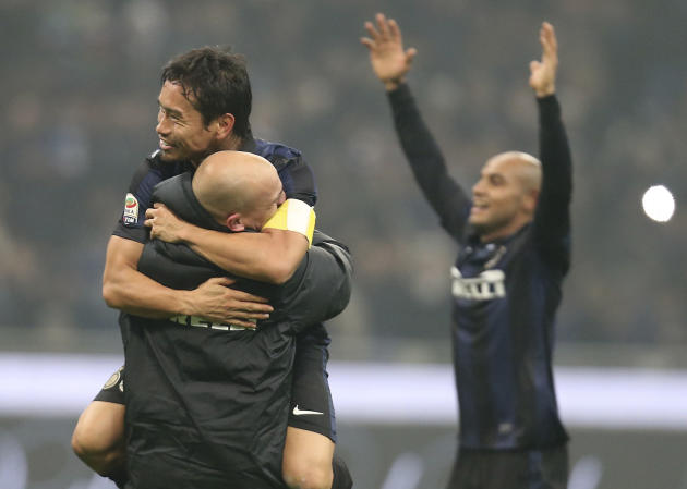 Inter Milan defender Yuto Nagatomo, top left, of Japan, hugs his teammates Argentine midfielder Esteban Cambiasso at the end of the Serie A soccer match between Inter Milan and AC Milan at the San Sir