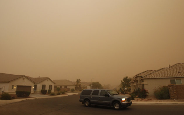 A vehicle drives through a brown cloud of blowing sand during a dust storm Monday, July 18, 2011, in Phoenix. The dust wall was about 3,000 feet high and created winds of 25 to 30 mph, with gusts of u