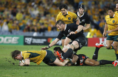 Hooper, captain of Australia's Wallabies, is tackled by New Zealand's All Blacks, including their captain McCaw, during their Rugby Championship match in Sydney