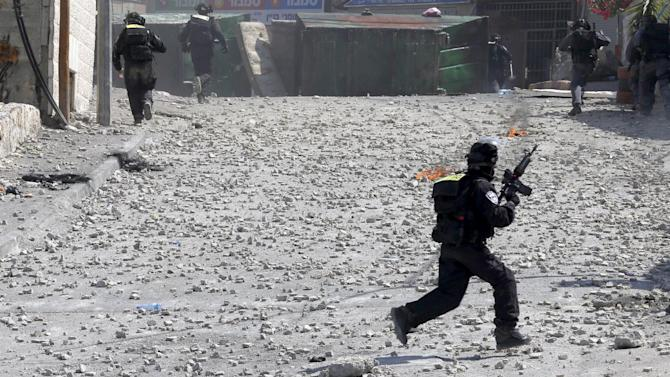 An Israeli police officer runs during clashes in the East Jerusalem neighbourhood of Issawiya