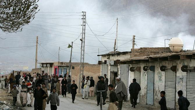 Local residents gather at a road as smoke rise from the site of a bomb blast in a market in Quetta, Pakistan on Saturday, Feb. 16, 2013. Senior police officer Wazir Khan Nasir said the bomb went off in a Shiite Muslim-dominated residential suburb of the city of Quetta. Residents rushed the victims to three different hospitals.(AP Photo/Arshad Butt)