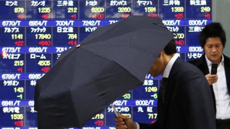 A pedestrian holding an umbrella walks past an electronic board displaying various stock prices outside a brokerage in Tokyo