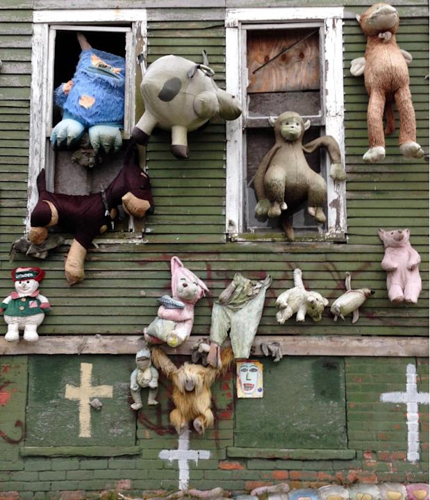 "In this Nov. 21, 2013 photo, stuffed animals are seen attached to ""The Party Animal House"" in the Heidelberg Art Project in Detroit. Another fire has burned a house that's part of the ou"