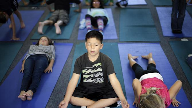 In this Dec. 11, 2012 picture, fourth grader Miguel Ruvalcaba holds a pose during a yoga class at Capri Elementary School in Encinitas, Calif. Administrators of the Encinitas Union School District are treading softly as they pioneer what is believed to be the first district-wide yoga program of its kind, while trying to avoid a legal dispute over whether yoga is just exercise or an intrinsically spiritual practice. (AP Photo/Gregory Bull)