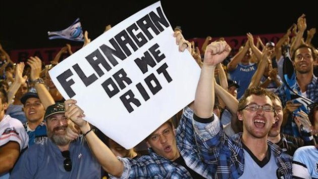 A Cronulla Sharks supporter holds up a sign in support of coach Shane Flannagan who was stood down by the club (Getty Images)