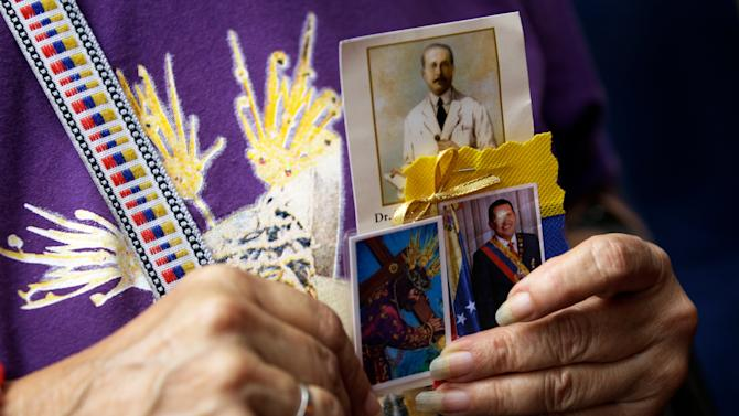 A woman holds a trio of images showing Venezuelan St. Jose Gregorio Hernandez, top, renowned as the ``Doctor of the Poor''; a laminated holy card of Jesus Christ; and an image of Venezuela's President Hugo Chavez, right, at a church service where supporters of the ailing president gathered to pray for his health, in Caracas,Venezuela, Thursday, Dec. 13, 2012.  Venezuelans were warned that Chavez may not be well enough after his fourth cancer-related surgery in Cuba to be inaugurated on Jan. 10.  (AP Photo/Fernando Llano)