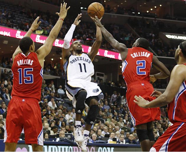 Memphis Grizzlies guard Mike Conley (11) shoots against Los Angeles Clippers center Ryan Hollins (15) and guard Darren Collison (2) in the second half of an NBA basketball game on Thursday, Dec. 5, 20