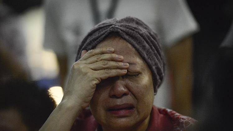 A woman reacts after hearing about the Malaysia Airlines passenger plane crashing in eastern Ukraine at Kuala Lumpur International Airport in Sepang, Malaysia, Friday, July 18, 2014.  Malaysia Airlines said it lost contact with Flight 17 over Ukrainian airspace Thursday. It was flying from Amsterdam to Kuala Lumpur, Malaysia. (AP Photo/Joshua Paul)