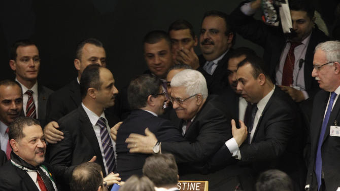 CORRECTS IDENTITY OF PERSON ABBAS EMBRACES==Palestinian President Mahmoud Abbas embraces Turkish Foreign Minister Ahmet Davutoglu  at the United Nations General Assembly after a vote on a resolution on the issue of upgrading the Palestinian Authority's status to non-member observer state in the United Nations in New York, Thursday, Nov. 29, 2012.  (AP Photo/Kathy Willens)