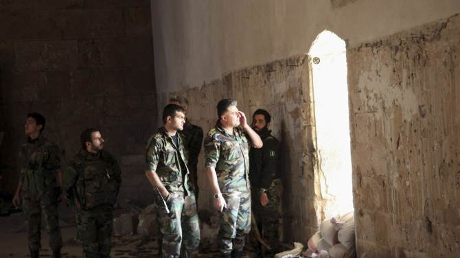 Forces loyal to Syria's President Bashar al-Assad take position inside Aleppo's historic citadel as they monitor the movements of rebel fighters who are positioned near the citadel