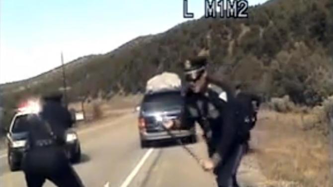 FILE - This file image from video provided by the New Mexico State Police shows three New Mexico State Police officers reacting as a minivan driven by motorist Oriana Farrell pulls away from a traffic stop that included one officer bashing the van's window with his night stick and another, Elias Montoya, at left, firing three shots at the fleeing van, Oct. 28, 2013. Montoya, a fired New Mexico State Police officer, says his heart sank when he learned after shooting at the minivan that there were children in the vehicle. Montoya says in an interview with ABC-TV that he wouldn't have fired at the vehicle if he had known even one child was inside. (AP Photo/New Mexico State Police, File)