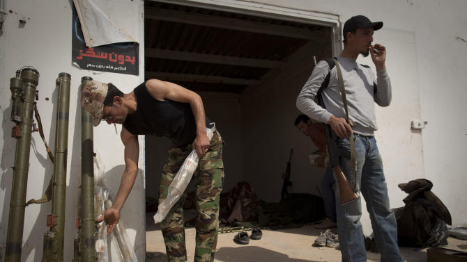 Libyan rebels clean up a checkpoint in the outskirts of Ras Lanouf, eastern Libya, Sunday, March 27, 2011.  Libyan rebels took back a key oil town and pushed westward Sunday toward the capital, seizing momentum from the international airstrikes that tipped the balance away from Moammar Gadhafi's military. Brega, a main oil export terminal in eastern Libya, fell after a skirmish late Saturday and rebel forces moved swiftly west, seizing the tiny desert town of Al-Egila  a collection of houses and a gas station on their way to the massive oil refining complex of Ras Lanouf. (AP Photo/Anja Niedringhaus)