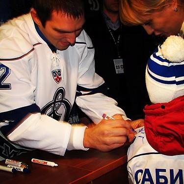 Alex Ovechkin signs a young fan's jersey