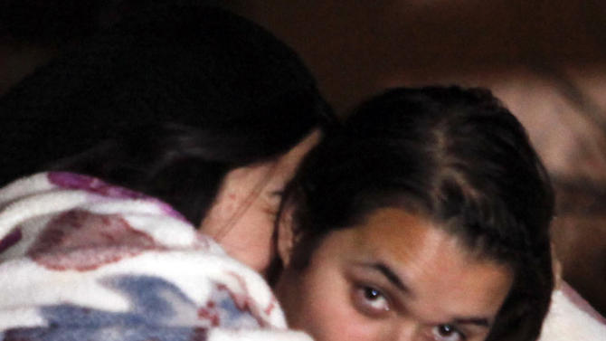 Jenicka Lopez, 15, daughter of Jenni Rivera, right, is hugged by Divine Rivera, niece of signer Jenni Rivera, left, during a news conference outside the home of Jenni Rivera's father in Lakewood, Calif., on Sunday, Dec. 9, 2012. Authorities have not confirmed her death, but Rivera's relatives in the U.S. say they have few doubts that she was on the Learjet 25 that disintegrated on impact Sunday in rugged territory in Nuevo Leon state in northern Mexico. (AP Photo/Patrick T. Fallon)