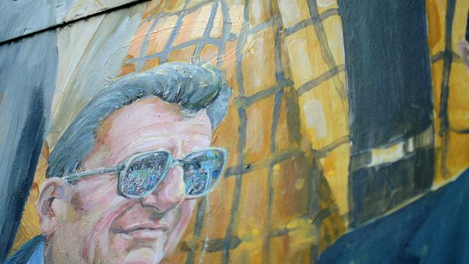 This Saturday, July 14, 2012 photo shows the edges of the newly-painted-over halo above the late Penn State football coach Joe Paterno on a mural by Michael Pilato in State College, Pa. Pilato removed the halo from the painting on Saturday amid the school's child sex-abuse scandal. (AP Photo/Centre Daily Times, Abby Drey)