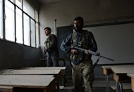 Syrian rebels take position in an empty school to observe regime forces in Aleppo on October 26. Two days ahead of key talks among the opposition in Qatar, the SNC lashed out at accusations from Washington that it was not fully representative of the country's diverse dissident forces