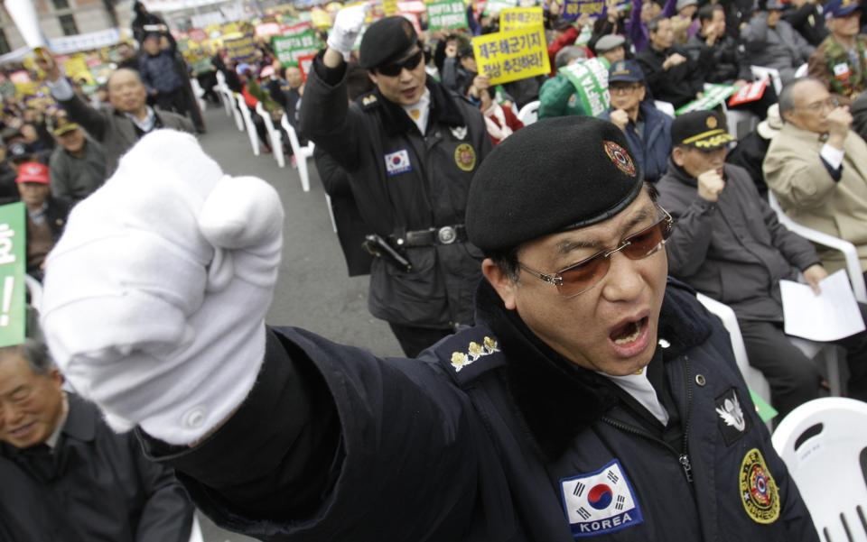 South Korean war veterans shout slogans during an anti-North Korea rally in Seoul, South Korea, Friday, March 16, 2012. North Korea announced it will launch a long-range rocket mounted with a satellite in honor of late President Kim Il Sung's April birthday. (AP Photo/Lee Jin-man)