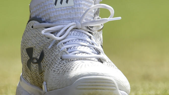 Andy Murray of Britain's wedding ring is tied into his shoe laces during his match against Ivo Karlovic of Croatia at the Wimbledon Tennis Championships in London