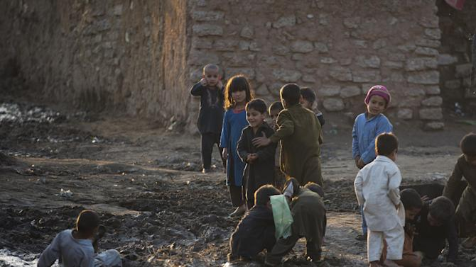 Pakistani children play on the ground after a rain in a suburb of Islamabad, Pakistan, Friday, March 6, 2015. The children are displaced with their parents from Pakistani tribal areas due to fighting between security forces and militants. (AP Photo/B.K. Bangash)