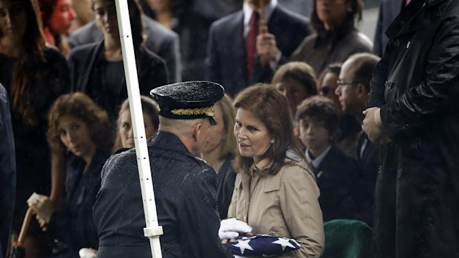Bonnie Englebardt Lautenberg, seated, right, widow of the late New Jersey Sen. Frank Lautenberg, is presented a U.S. flag by Army Major Gen., Michael S. Linnington, left, kneeling, during burial services at Arlington National in Arlington, Va., Friday, June 7, 2013. Lautenberg, who died Monday at age of 89 after suffering complications from viral pneumonia, was the last World War II veteran in the Senate. (AP Photo/Pablo Martinez Monsivais)