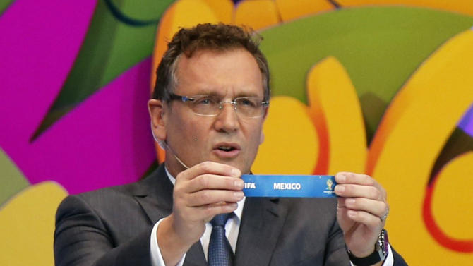 """FIFA Secretary General Jerome Valcke holds the slip showing """"Mexico"""" during the draw for the 2014 World Cup at the Costa do Sauipe resort in Sao Joao da Mata"""