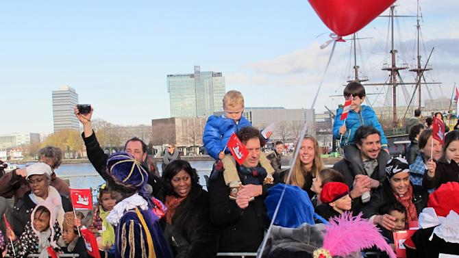 """In this photo taken Sunday, Nov. 18, 2012 persons dressed as """"Zwarte Piet"""" or """"Black Pete"""" attend a parade after St. Nicholas, or Sinterklaas, arrived by boat in Amsterdam, Netherlands. Foreigners visiting the Netherlands in winter are often surprised to see that the Dutch version of St. Nicholas' little helpers resemble a racist caricature of a black person. The overwhelming majority of Dutch, who pride themselves on tolerance, are fiercely devoted to their holiday tradition and say """"Zwarte Piet"""", whose name means """"Black Pete"""", is absolutely harmless, a fictional figure who does not represent any race. But now a growing group of Dutch natives are questioning whether this particular part of the tradition should be changed. (AP Photo/ Margriet Faber)"""