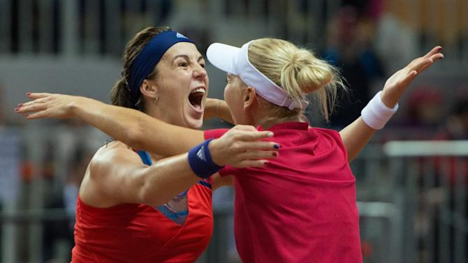 Russia's Anastasia Pavlyuchenkova, left, and Elena Vesnina congratulate each other after their winning Fed Cup semifinal tennis match against Germany's Andrea Petkovic and Sabine Lisicki in Sochi, Russia, Sunday, April 19, 2015. They won 6-2, 6-3. (AP Photo/Artur Lebedev)