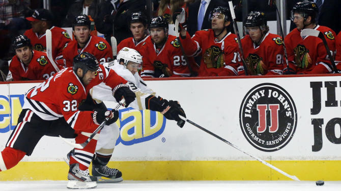Chicago Blackhawks defenseman Michal Rozsival (32), of the Czech Republic, and Anaheim Ducks center Nick Bonino battle for the loose puck during the first period of an NHL hockey game, Tuesday, Feb. 12, 2013, in Chicago. (AP Photo/Charlie Arbogast)