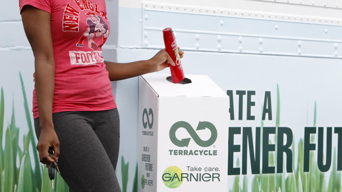 A guest recycles her used Garnier product in the TerraCycle and Garnier recycling bin outside The Garnier Greener Tour Bus on Saturday June 16, 2012 in Houston. (Photo by Aaron M. Sprecher/Invision for Garnier/AP Images)