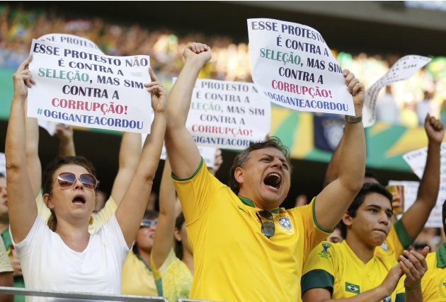 Protesters cheer as they hold signs during the Confederations Cup Group A soccer match between Brazil and Mexico at the Estadio Castelao in Fortaleza