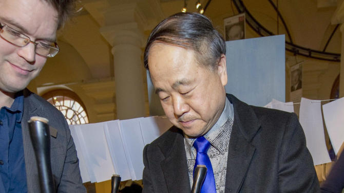 The 2012 Nobel Literature Prizewinner, Mo Yan of China, right, traditionally signs his chair at the Nobel Museum in Stockholm, Thursday Dec. 6, 2012. The chair signing is one of the traditions during the week leading up to the Nobel Prize ceremony that will take place in Stockholm on Dec. 10. (AP Photo/Fredrik Sandberg, Scanpix) SWEDEN OUT