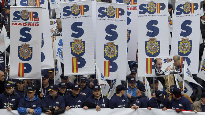 "Police march holding union flags and a banner reading, ""all the police united against the financial cuts"" during a protest  against government's austerity measures and the elimination of their Christmas bonus pay, one of 14 paychecks that most Spanish civil servants get each year, in Madrid, Spain, Saturday, Nov. 17, 2012. (AP Photo/Andres Kudacki)"