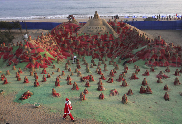 A man dressed in a Santa Claus costume walks past sand sculptures of Santa Clauses created by artist Pattnaik and his students as part of Christmas celebrations on a beach in Puri