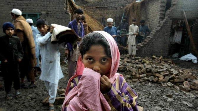 People salvage what they can from a house that collapsed from heavy rain and windstorm that reached up to a speed of 120 kph (75 mph) Sunday evening which collapsed hundreds of buildings, uprooted trees, and electric poles, in Peshawar, Pakistan, Monday, April 27, 2015. (AP Photo/Mohammad Sajjad)