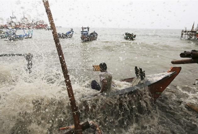 Fisherman falls in his wooden boat as it is hit by strong sea waves, and breaks, in water off the north coast of Jakarta