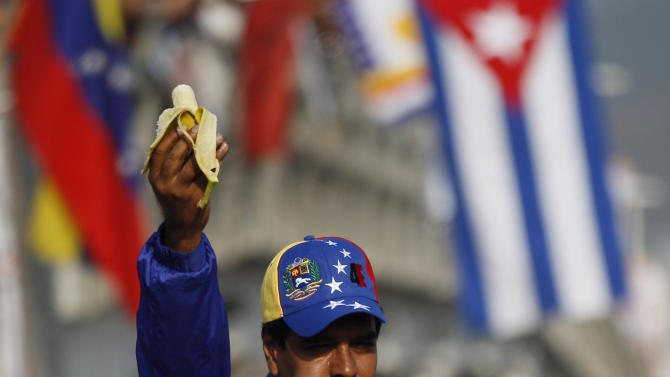 Venezuela's acting President Nicolas Maduro eats a banana during a presidential election campaign rally in Catia La Mar, Vargas state, Venezuela, Tuesday, April 9, 2013.  Maduro, the hand-picked successor of late President Hugo Chavez, is running for president against opposition candidate Henrique Capriles in the presidential election set for Sunday, April 14. (AP Photo/Ariana Cubillos)