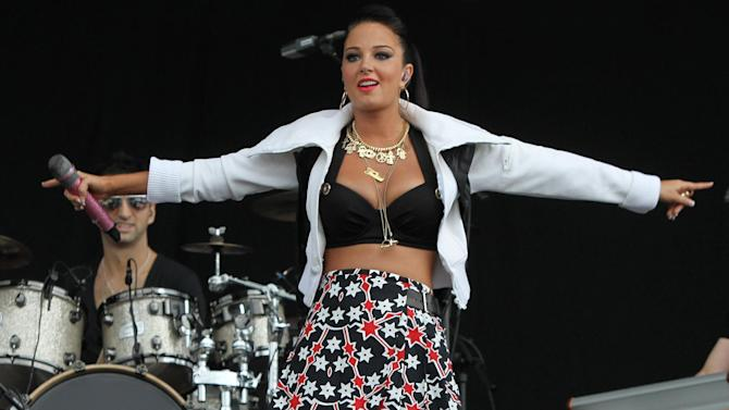 """FILE - A Saturday, July 7, 2012 photo from files showing British singer Tulisa Contostavlos performing on stage at the 2012 Wireless Music Festival in Hyde Park, central London. British media said Tuesday, June 4, 2013 that singer and former """"X Factor"""" judge Tulisa Contostavlos has been arrested over allegations of supplying hard drugs. The arrest comes after the Sun tabloid ran a story claiming the 24-year-old had acted as a go-between in a deal to sell cocaine. The Metropolitan Police force said a 24-year-old woman and a 35-year-old man were arrested """"on suspicion of being concerned with the supply of class A drugs"""" and were being questioned. (AP Photo/Joel Ryan, File)"""